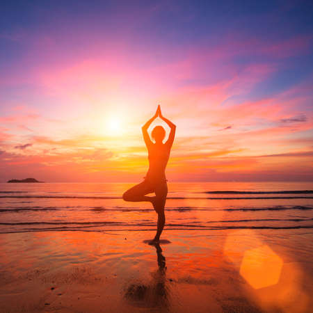 yoga beach: Silhouette of a young woman practicing yoga in the rays of the surrealist sunset at the seaside.