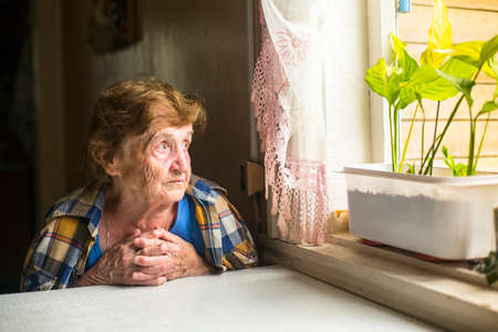 Lonely old woman sitting by the window in his cottage. Stock Photo