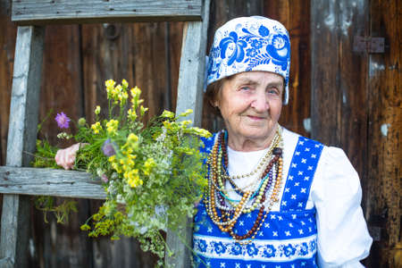 70 75 years: Slavic old woman in ethnic clothes outdoor. Grandmother.