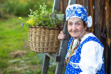 75 80: Slavic happy elderly woman in ethnic clothes outdoor in the village. Grandmother.