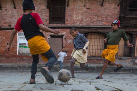sanskrit: KATHMANDU, NEPAL - DEC 9, 2013: Unknown children play football after lesson at Jagadguru School. School established at 2013, to let new generation learn Sanskrit and preserve Hindu culture. Editorial