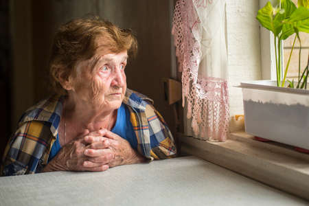 Old lonely woman sitting near the window in his house. photo