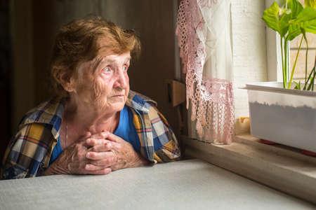 Stary samotna kobieta siedzi przy oknie w swoim domu.