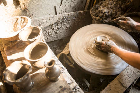 BHAKTAOUR, NEPAL - DEC 7, 2013: Unidentified Nepalese man working in the his pottery workshop. More 100 cultural groups have created an image Bhaktapur as Capital of Nepal Arts.