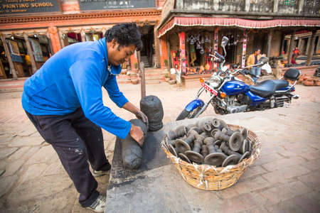 rotates: BHAKTAOUR, NEPAL - DEC 7, 2013: Unidentified Nepalese man working in the his pottery workshop. More 100 cultural groups have created an image Bhaktapur as Capital of Nepal Arts.