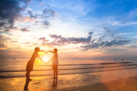Young couple of lovers on a tropical beach holding hands forming a heart.
