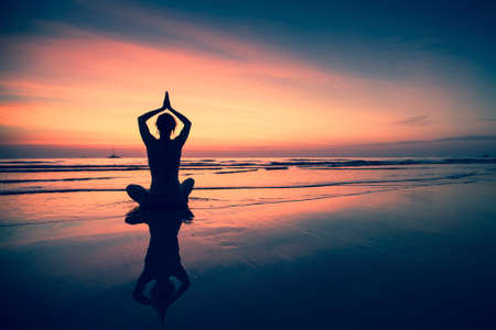 Silhouette of woman practicing yoga during surrealistic sunset at the seaside. Stockfoto