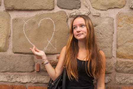 Teen girl in frustration standing against the wall with the drawn heart. Broken love concept. photo