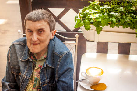cerebral palsy: Disabled man with cerebral palsy, smiling sitting at an outdoor cafe.
