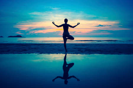 and harmony: Silhouette young woman practicing yoga on the beach at surrealistic sunset. Stock Photo