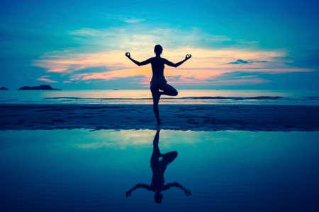 armonia: Silueta de la mujer joven a practicar yoga en la playa al atardecer surrealista.