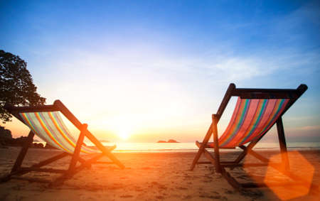loungers: Pair beach loungers on the deserted coast sea at sunrise. Vacation concept.