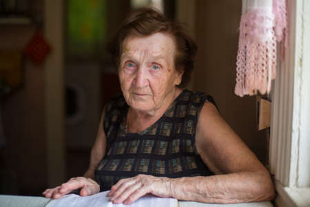 anxious face: Worried elderly woman sitting at table in the house.