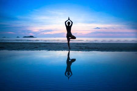 Silhouette junge Frau praktizieren Yoga am Strand bei Sonnenuntergang surrealistisch.