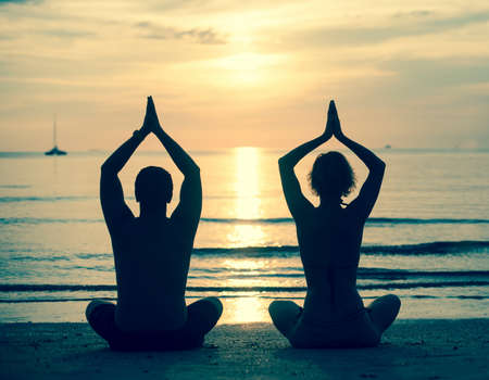 Silhouette of young couple practicing yoga on sea beach during sunset. Cross-process photo style. Standard-Bild