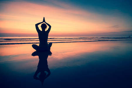 Silhouette young woman practicing yoga on beach at surrealistic sunset. Stockfoto