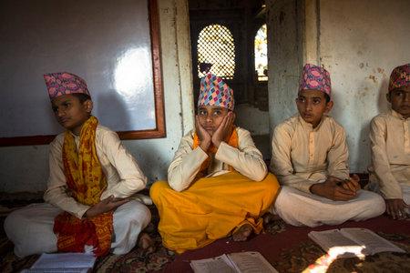 sanskrit: KATHMANDU, NEPAL - DEC 9, 2013: Unknown people during the reading of texts in Sanskrit at Jagadguru School. School established at 2013 to let preserve Hindu culture.