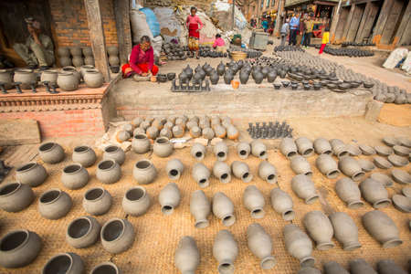 BHAKTAPUR, NEPAL - DEC 7, 2013: Unidentified Nepalese people in the his pottery workshop. More 100 cultural groups have created an image Bhaktapur as Capital of Nepal Arts.