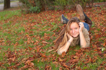 only one girl: Cute teen girl lying on autumn ground with yellow falling leaves. Stock Photo