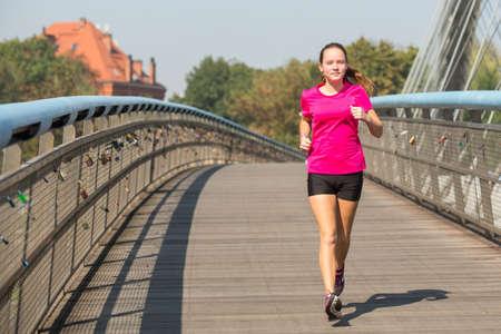 girl sport: Running girl. Young girl runner on the bridge in European city. Stock Photo