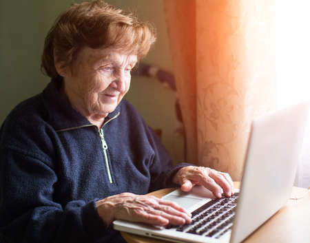 Grandmother near the window works with a laptop.