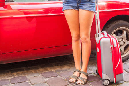 Abstract young girl near a car with a red suitcase. photo