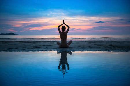 Yoga, silhouette of meditating woman.