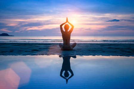 Yoga on the sea beach, meditation.
