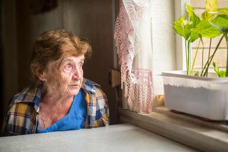 자신의 집에 창문 근처에 혼자 앉아 늙은 여자. 노년의 외로움.