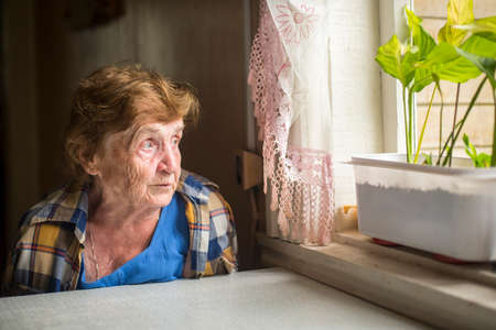 Old woman sitting alone near the window in his house. Loneliness in old age. Archivio Fotografico