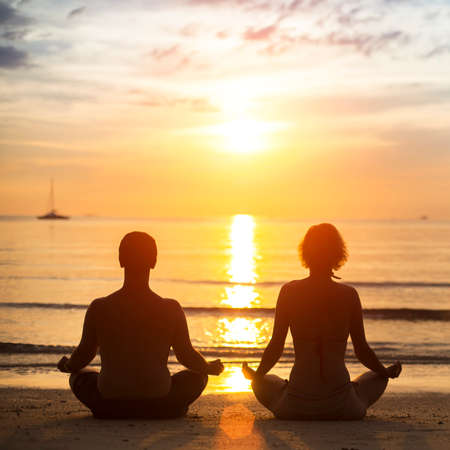 yoga meditation: Yoga couple meditating on the sea beach.