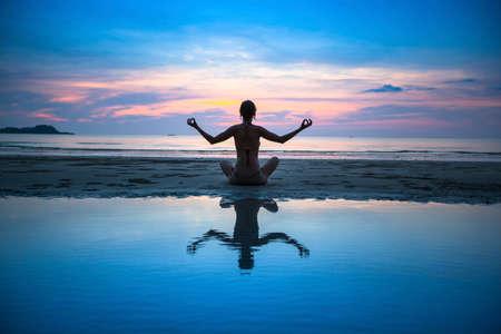 Schattenbild der Yoga-Frau meditiert am Meeresstrand. Yoga und Fitness. Standard-Bild