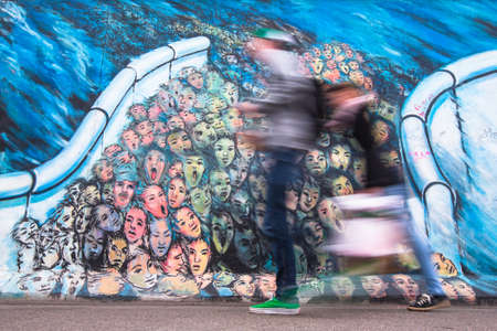 largest: BERLIN, GERMANY - NOV 15, 2014: Fragment of graffiti on Berlin Wall at East Side Gallery - its a 1.3 km long part of original Wall which collapsed in 1989 and now is largest world graffiti gallery.