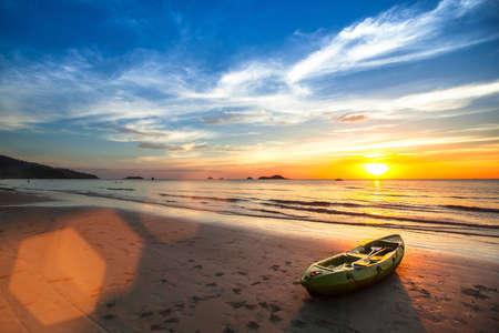ocean kayak: Paisaje tropical. Canoa en la playa del oc�ano durante la puesta de sol incre�ble. Foto de archivo
