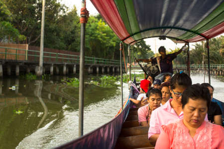 praya: BANGKOK, THAILAND - DEC 19, 2014: A long-tail boat carrying local people passing on the Chao Praya River. Long-tail boats are a cheap (15 baht $0,5) form of river transport in the Thai capital.