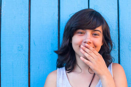 teenage girl: Teen girl covers her mouth with her hand, on the background of blue wooden walls.