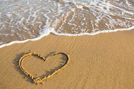 evoking: Heart drawn on the sand of a beach.