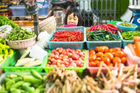 BANGKOK, THAILAND - DEC 15, 2014: Unidentified girl child seller on the Burmese street market in Bangkok. There is 16,000 registered street vendors in Bangkok. Редакционное
