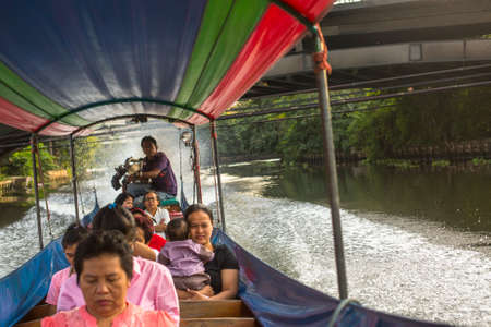 0 to 5: BANGKOK, THAILAND - DEC 19, 2014: A long-tail boat carrying local people passing on the Chao Praya River. Long-tail boats are a cheap (15 baht $0,5) form of river transport in the Thai capital.