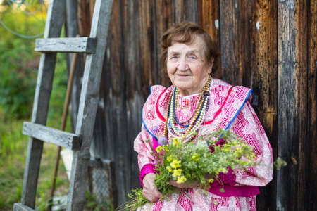 ethnic dress: Old positive woman in the village, in a festive ethnic dress.