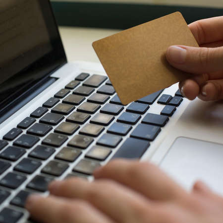 entering information: Credit card (with place for your text) in hand and entering security code using laptop keyboard. Stock Photo