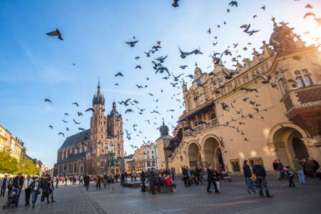 assumed: KRAKOW, POLAND - NOV 11, 2014: Unidentified people near the Church of Our Lady Assumed also known as St. Marys Church at the Main Market Square in Krakow, Poland.
