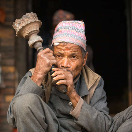 BHAKTAPUR, NEPAL - DEC 7, 2013: Portrait of unidentified Nepalese man smokes on the street. More 100 cultural groups have created an image Bhaktapur as Capital of Nepal Arts.
