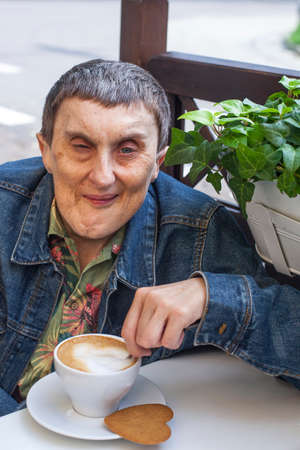 cerebral palsy: Portrait of disabled man with cerebral palsy sitting at outdoor cafe and drinking coffee.