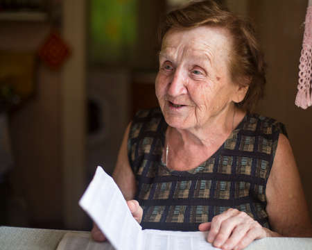 talks: Old woman emotionally talks and reads in a notebook in his house.