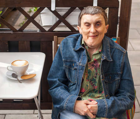 cerebral palsy: Disabled man with cerebral palsy sitting at outdoor cafe with a cappuccino. Stock Photo