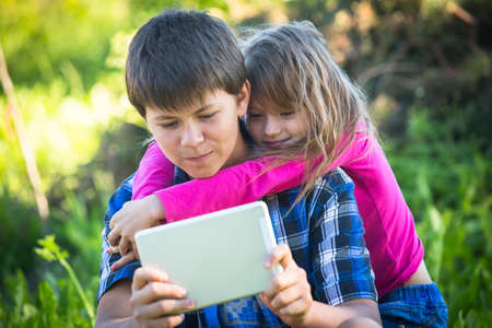 Teenager boy with tablet and his younger sister, outdoors. photo
