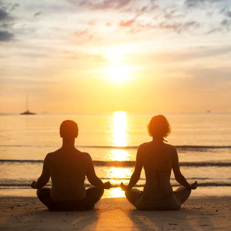Young yoga couple is meditating in the Lotus position on the sea beach during sunset. photo