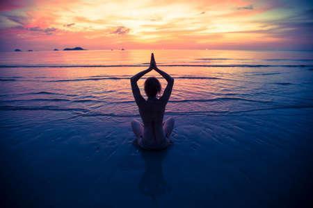 Yoga silhouet, oefeningen op het strand. Stockfoto