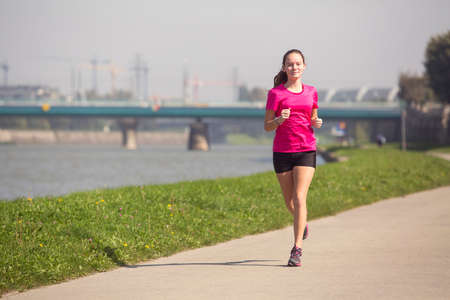 jogging track: Young girl runs on Jogging track along the river in a big city. A healthy way of life.